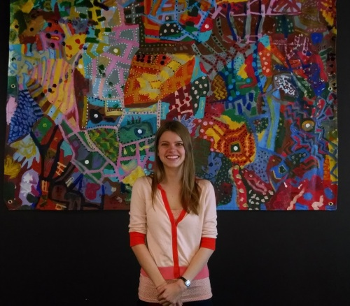 Intern Claire in front of artwork by AWE.
